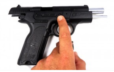 Step 2: Locate the take down pin and apply pressure inwards toward the gun. Pushing the pin through the B6P 9mm handgun will get easier with time. It will be difficult to do at first. We've noticed that if we relieve a bit of pressure off of the slide, the pin does come out a bit easier.